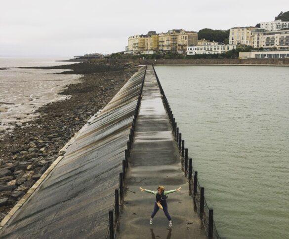 Liz standing on a walkway in between the sea and reservoir