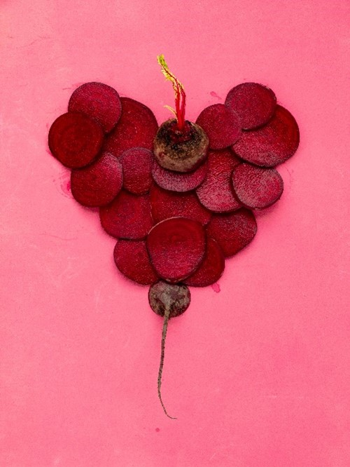 beets in the shape of a heart on a pink background