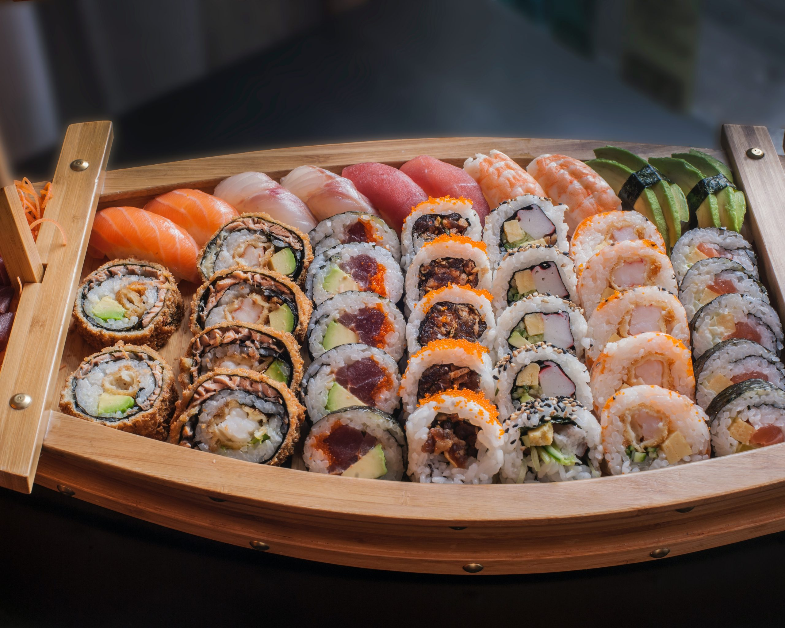 a variety of sushi in a small boat like platter