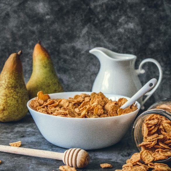 cereal in a bowl with a jug and two pears next to the bowl