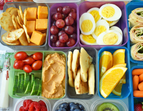 lunchboxes filled with eggs, fruit, veg, cheese and crackers